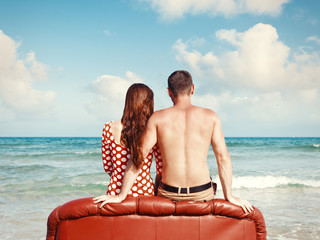 couple resting on leather couch on the beach