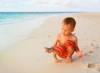 little boy holding starfish on sunset beach