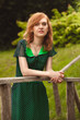 portrait of redhead woman in green dress on wooden bridge