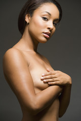 Nude Hispanic woman with arms covering breasts