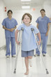 Nurses watching boy with broken leg walk with crutches