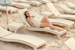 woman in dress lying on sunbed at empty beach