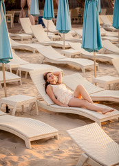 elegant woman relaxing on beach at hotel resort