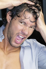 Close up of young man yelling with hands on head