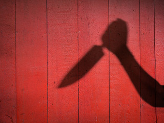 Male Hand Shadow with Kitchen Knife, on concrete wall