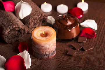 SPA concept: chocolate mudpack, rose petals, candle and towels