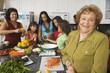 Large Hispanic family in kitchen preparing food