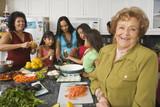 Fototapety Large Hispanic family in kitchen preparing food