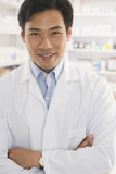Asian male pharmacist standing in pharmacy
