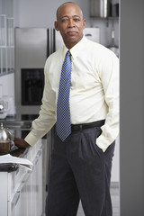 Senior African businessman standing in kitchen