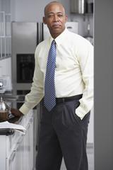 Senior African businessman standing in kitchen