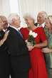 Senior man giving wife bouquet of flowers while friends watch