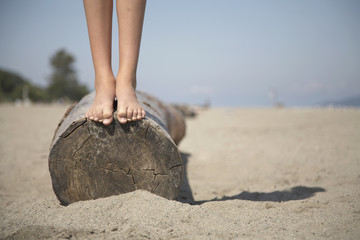 Close up of girl standing barefoot on log at beach