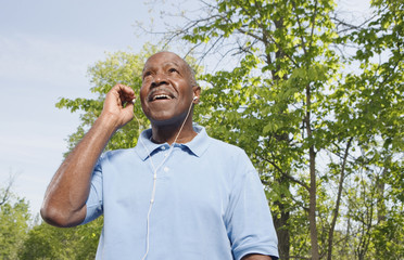 Low angle view of senior African man with mp3 player outdoors