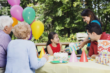 Hispanic girl receiving gifts at birthday party