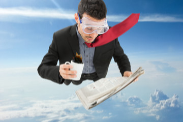 Businessman skydiving while reading a newspaper