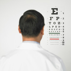 Rear view of Asian man looking at eye chart