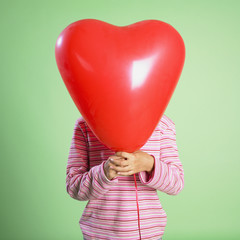 Hispanic girl holding balloon in front of face