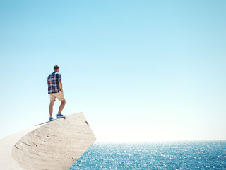 Young man standing on a peak and sea