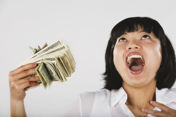 Asian woman fanning self with money