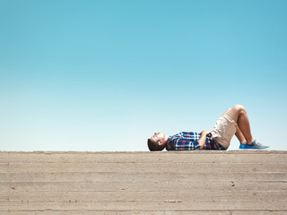 Man lying on cement wall