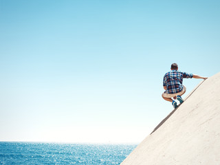 Young man sitting on a peak and sea