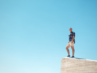 Young man standing on a peak and desert