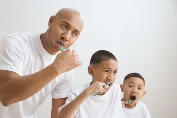 Indian father and sons brushing teeth