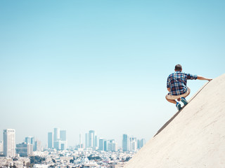 Young man sitting on a peak and city