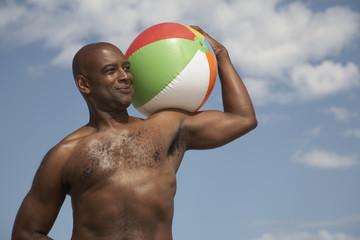 Portrait of African man holding beach ball