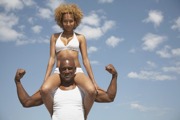 African man carrying wife on shoulders