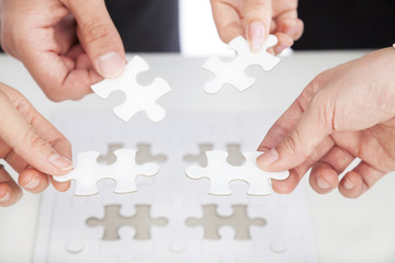 Business team Holding Jigsaw Puzzle on the desk