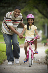 African father helping daughter ride bicycle
