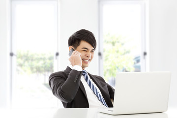 young business man talking happily by smart phone in office