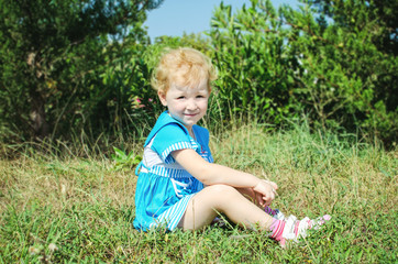 beautiful little smiling girl posing outdoors in summer park. Ad