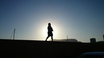 Silueta de mujer paseando por puerto deportivo