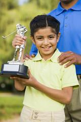 Hispanic girl holding golf trophy