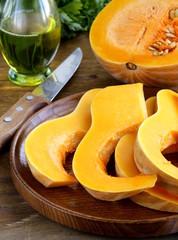 fresh raw pumpkin sliced on a wooden table