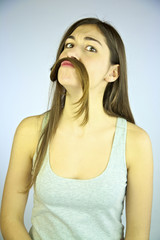 Young female model having fun playing with hair like moustache