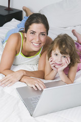 Mother and daughter with laptop on bed