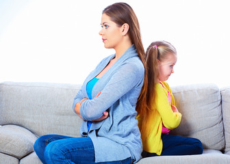 Woman with girl seating on sofa back to back.