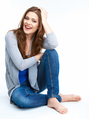 Smiling woman sitting on a white floor.