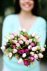 Closeup portrait of a woman holding flowers. Focus on flowers