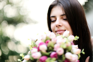 Portrait of a young beautiful woman smelling flowers