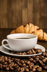 cup of coffee with coffee beans and croissant