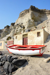 Santorini, Greece: a fisherman boat under the volcanic cliffs
