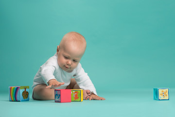 Little cute baby boy playing with color blocks