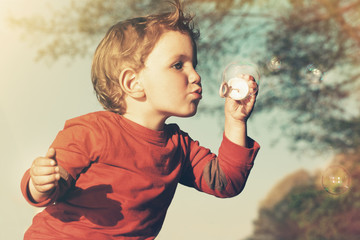 Little boy blowing soap bubbles