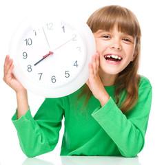 Little girl is holding big clock