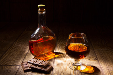 Bottle and a glass of brandy with chocolate